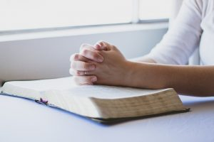 woman praying with her Bible open